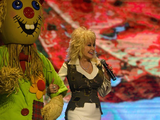 Dolly Parton walks on stage Friday, Aug. 18, 2017 to