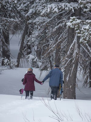 A couple walks in the fresh snow near the summit of the Mt. Rose Highway on Monday, February 26, 2018.