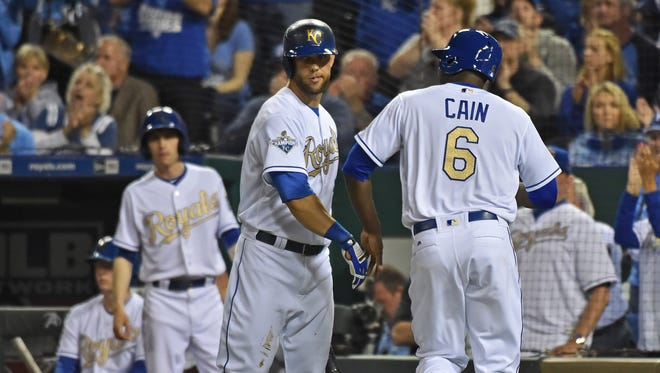 Lorenzo Cain gets a hand from teammate Alex Gordon after scoring.