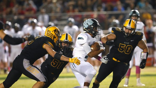 Highland's Tyrus Bryant (3) tries to avoid being tackled by  Gilbert's Tyler Laganke (6), Tyler Moore (51) and Manuel Meza (50) during a high school football game at Gilbert High on October 20, 2017.