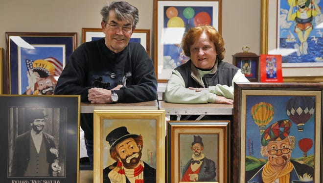 Terry and Lea Locke, owners of G & L Auction Service, stand among some of the Red Skelton art prints that will be sold at auction April 22 in Appleton. The auction will include five original pieces by Skelton.