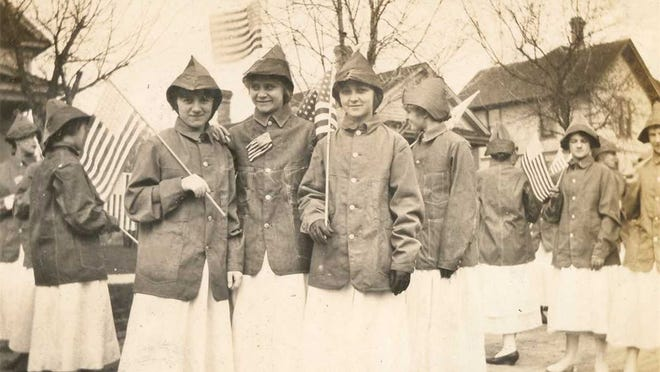 Photo taken by John T. Matschi of employees of Oshkosh B'Gosh lined up on a south-side street in preparation for a patriotic parade held in Oshkosh at the beginning of WW 1. The women wore dungaree jackets and caps holding American flags