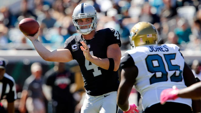 Oakland Raiders quarterback Derek Carr (4) throws a side arm pass around Jacksonville Jaguars defensive tackle Abry Jones (95) during the second half of  a football game at EverBank Field.
