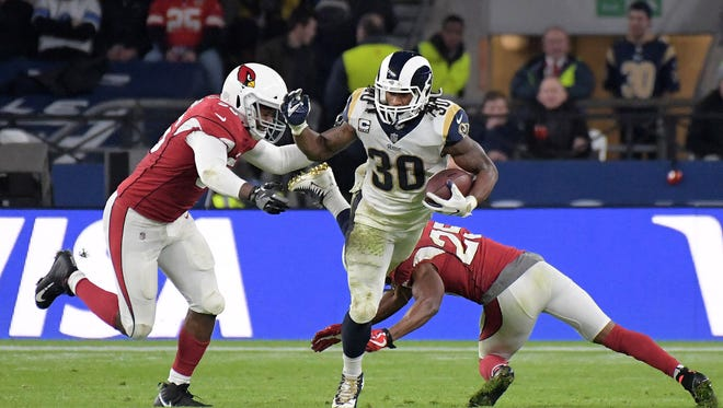 Los Angeles Rams running back Todd Gurley (30) is defended by Arizona Cardinals inside linebacker Karlos Dansby (56) and defensive back Tramon Williams (25).