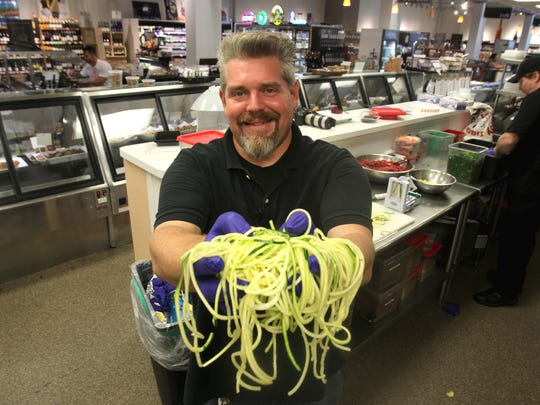 An Ada's chef displays spiraled zucchini for the market's dairy, soy and wheat-free raw vegan zucchini pesto pasta.