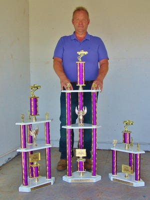 Steve Hall poses with trophies that he donated to the 2016 Summer Rough Truck Contest held at the Coshocton County Fairgrounds.