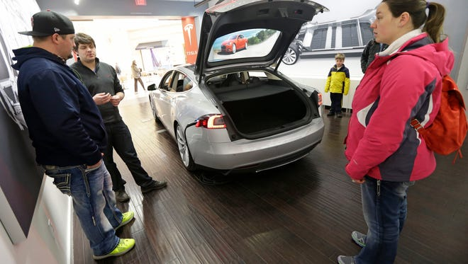 Robert Reynolds, left, and his wife Sarah, right, are shown a new Tesla all electric car by Tesla representative John Van Cleave, Monday, March 17, 2014, at a Tesla showroom inside the Kenwood Towne Centre in Cincinnati. Indiana, which has similar showrooms, will allow more direct sales like this -- for now