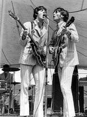 Paul McCartney (left) and John Lennon perform with the Beatles at Crosley Field.
