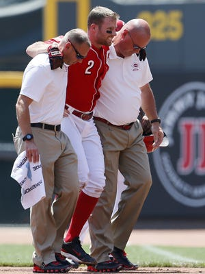 Reds shortstop Zack Cozart is carried off the field by trainers after tumbling while being thrown out at first base during the bottom of the first inning Wednesday against the Phillies.