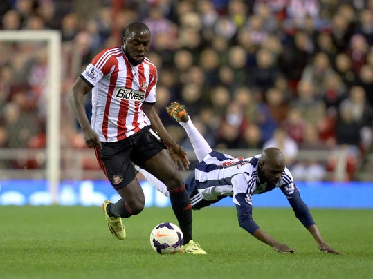 FILE - In a May 7, 2014, file photo Sunderland's Jozy Altidore, left, vies for the ball with West Bromwich Albion's Youssouf Mulumbu, right, during their English Premier League soccer match at the Stadium of Light, Sunderland, England.  As the Americans prepare for next month's World Cup tournament in Brazil, pressure for goals will be on Altidore  (AP Photo/Scott Heppell/file)