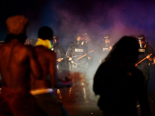 Officers stand in formation in front of protesters in Charlotte, N.C. on Tuesday, Sept. 20, 2016. Authorities used tear gas to disperse protesters in an overnight demonstration that broke out Tuesday after Keith Lamont Scott was fatally shot by an officer at an apartment complex. (Jeff Siner/The Charlotte Observer via AP)