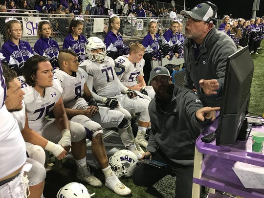 Shasta High School football coaches show some Wolves on the sidelines their gameplan at the state championship game Saturday night in Thousand Oaks.