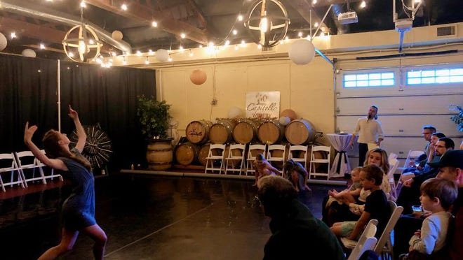 Sarah Klosterman performs for audience members at Capitello Winery while Antonio Anacan, rear, emcees at one of #instaballet's 2019 First Friday events.