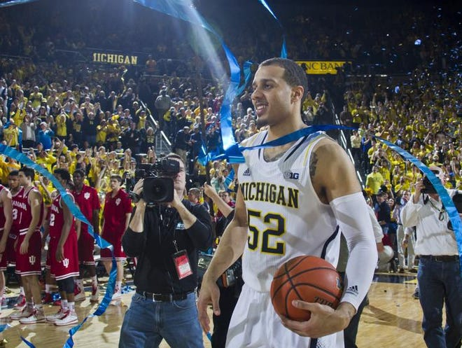 Michigan forward Jordan Morgan (52) holds the game ball as confetti falls in the arena at the end of an NCAA college basketball game against Indiana at Crisler Center in Ann Arbor, Mich., Saturday, March 8, 2014. Michigan won 84-80, and celebrated their outright Big Ten regular season championship. (AP Photo/Tony Ding)