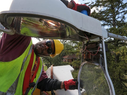 Detroit streetlight maintenance worker Leonard Robinson changes out streetlights and photo cells on Detroit's west side on Sept. 30, 2013. As many as 40% of the city's 88,000 street and alley lights are estimated to be out.