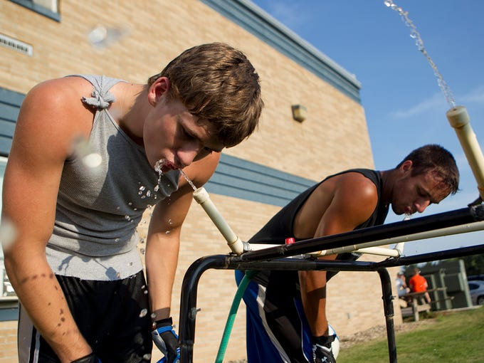 Shane Randl, left, and Dylan Peplinski, right, grab a drink of water between drills during football practice at Auburndale High School, Wednesday, Aug. 6, 2014.