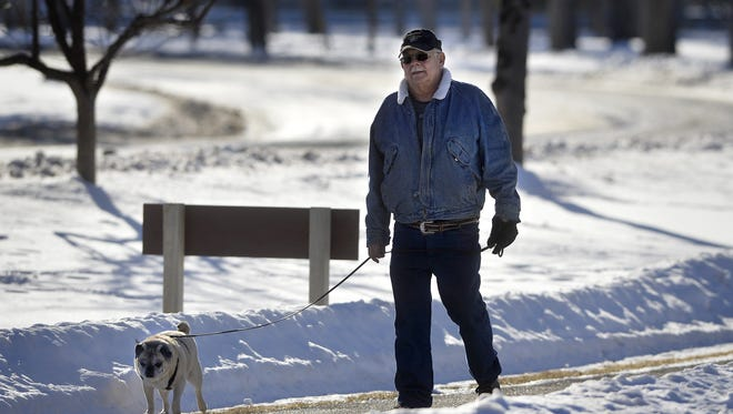 Robert Paranteau walks his dog Bandit at Gibson Park on Thursday afternoon.