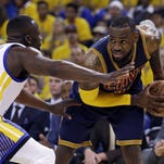In this June 14 photo, Cleveland Cavaliers forward LeBron James, right, is guarded by Golden State Warriors forward Draymond Green during the first half of Game 5 of basketball's NBA Finals in Oakland, California. A person with knowledge of the decision tells The Associated Press that James will not exercise a $21.6 million option on his contract, making him a free agent on July 1.