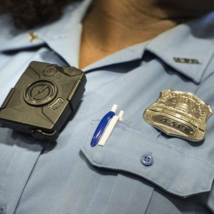 Washington DC Police Officer Debra Domino models a body camera before a press conference at City Hall September 24, 2014 in Washington, DC.