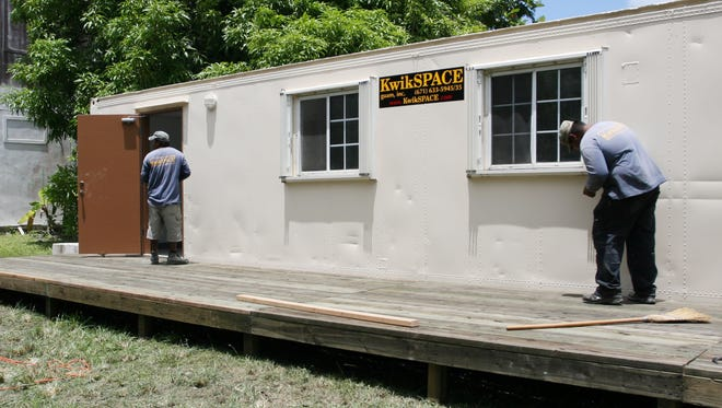 In this April 2008 photo, Kwikspace workers put the finishing touches on temporary kitchen facilities donated to Kamalen Karidat. Kwikspace has filed a patent infringement lawsuit against Reaction Co.