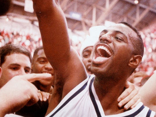 11/27/1993 -- Butler University Jermaine Guice  raises his hand high into the air with a big   smile  as he is mobbed by fans after   Butler  defeated IU   75-71.
