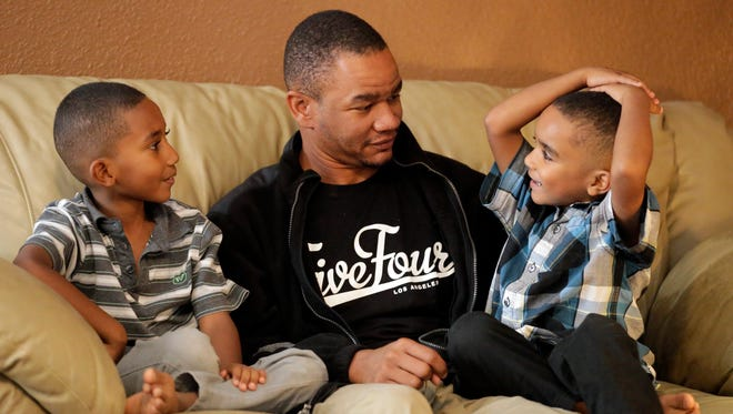 Neomiah, Ryan and Ezekiel Hawk share a moment together on the family's couch. The Hawks are finalizing the adoption of Ezekiel, 6, on Saturday as part of National Adoption Day.