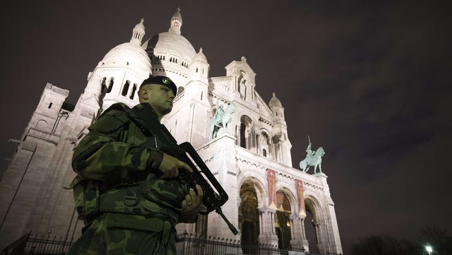 A French soldier enforcing the Vigipirate plan, France's national security alert system, patrols in front of the Sacre Coeur Basilica on November 16, 2015 in Paris.