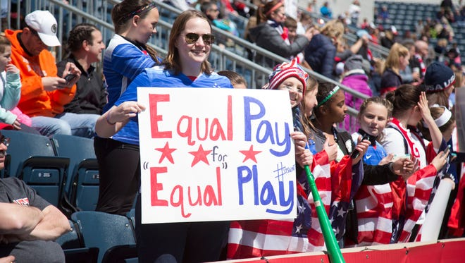"""A fan of the United States holds a sign that reads, """"Equal pay for equal play"""" during the game against Colombia on April 10, 2016 in Chester, Pennsylvania."""