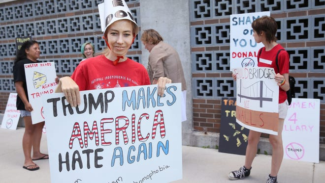 Protester Janet Helgesen of Green Bay along with others protest near the KI Convention Center in Green Bay, Wi. prior to Donald Trump and Mike Pence's rally on Friday.  Several were demonstrating across the street while supporters waited to get into the venue.