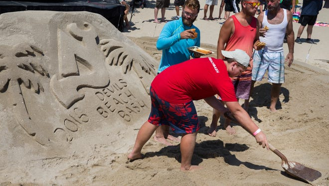 Worker puts the finishing touches on a Devils Beach Bash sand sculpture. Devils Beach Bash at the North Inlet of Jenkinson's Boardwalk where former Devil player Ken Daneyko and the Devils Miles Wood and Joe Blandisi talked with the crowd and signed autographs.