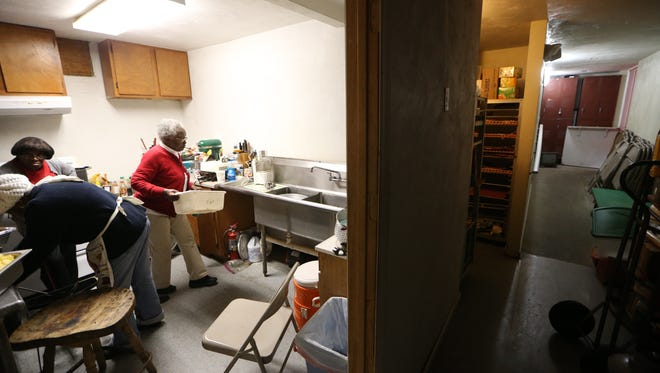 Annie Johnson works with volunteers to cook and peel potatoes Tuesday in a small kitchen packed with donated food for Thanksgiving. The effort is a part of Project Annie, an initiative she started in 1998 to feed those in need in the Frenchtown neighborhood.