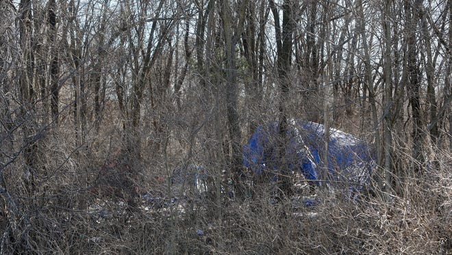 "A tarp and tents can be seen through the trees at a homeless camp known as ""Hobo Junction"" off of Chestnut Expressway east of Kansas Expressway in February of 2017."
