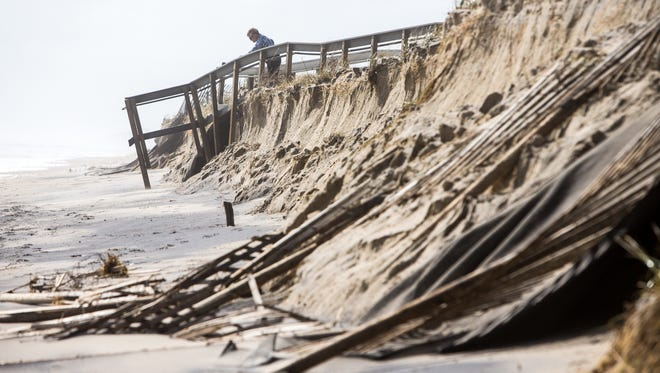 A woman peeks over the edge as the weekend storm caused damage to the dunes allow South Bethany beach where debris is scattered throughout the area.