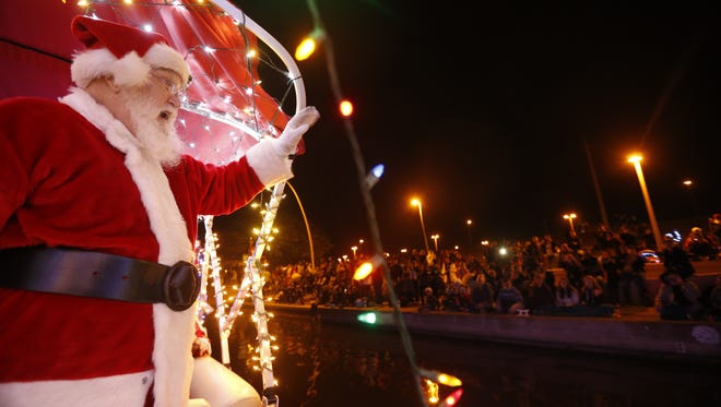 Santa waves to kids during the Fantasy of Lights Boat Parade on the Tempe Town Lake on Dec. 9, 2017 in Tempe.