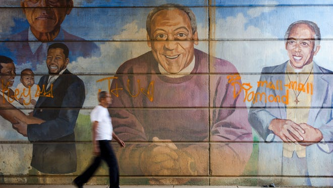 A man walks past a mural depicting entertainer Bill Cosby, center, in Philadelphia on July 8, 2015.