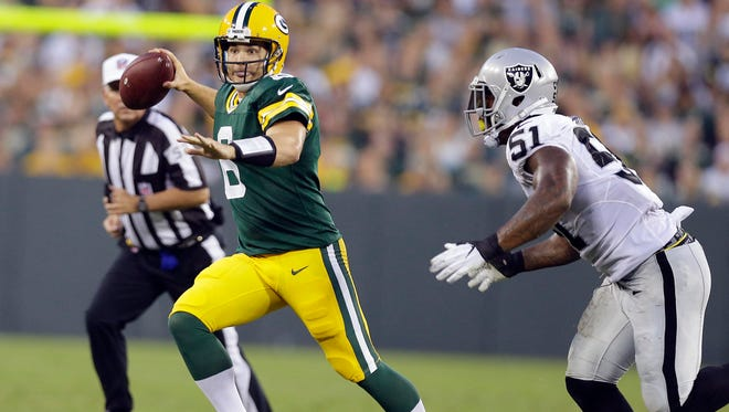 Green Bay Packers quarterback Joe Callahan struggles to get a pass off while being pursued by Oakland Raiders linebacker Bruce Irvin.