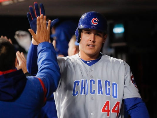 Chicago Cubs' Anthony Rizzo celebrates in the dugout after hitting the game-tying three-run home run off Cincinnati Reds relief pitcher Michael Lorenzen during the ninth inning of a baseball game, Friday, April 21, 2017, in Cincinnati. The Cubs won 6-5 in 11 innings. (AP Photo/John Minchillo)