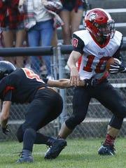 East's quarterback Alex Becker, right, avoids tackle