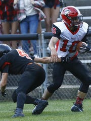East's quarterback Alex Becker, right, avoids tackle