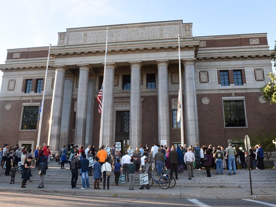A crowd gathers around the Stearns County Courthouse