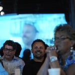 """Island House Restaurant owner Blake Johnson (center) watches an episode of Food Network's """"Beach Eats USA"""" that featured his Wachapreague, Virginia restaurant on Wednesday, Sept. 16, 2015. The restaurant held a viewing party for the airing of the show hosted by Chef Curtis Stone and featured Johnson and Executive Chef Michael Kane."""