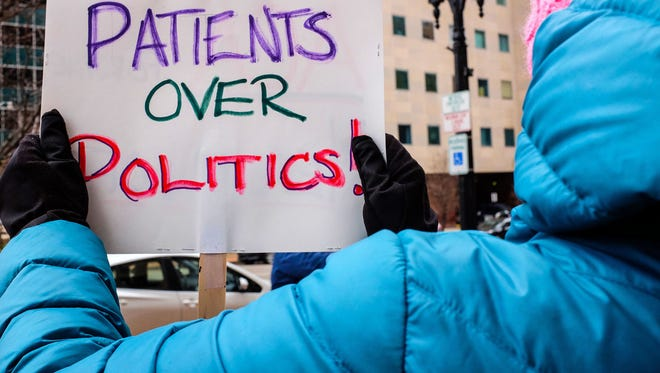 A woman holds a sign while demonstrating in downtown Lansing, Mich., with a group of health care professionals who favor keeping and fixing the Affordable Care Act.