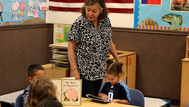 Donna Livensparger, an early interventionist II at the Mosaic of San Angelo, talks with children in the classroom during reading time Wednesday, March 29.