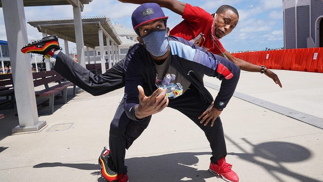 "Hip Hop street performers Eric ""Official Shine"" Watson, top, and YAK Anonymous Entertainment, Geno ""G Tha Blast"" Johnson, warm up before a show at Hampton Beach Thursday afternoon."