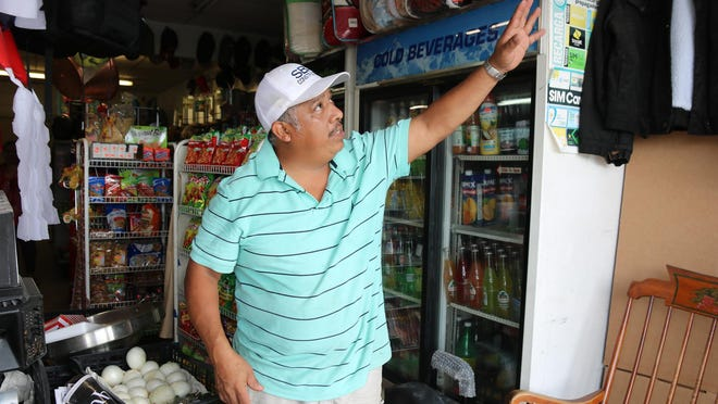 Las Estrellitas owner Jose Resendiez looks at damages at the front of his store where a car hit Wednesday night in Pink Hill.