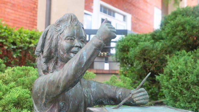 A statue of a girl painting sits outside the Community Council for the Arts in Kinston at 400 N. Queen St.