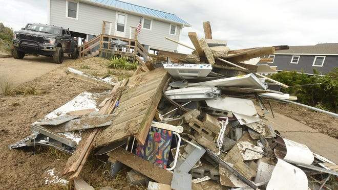 Crews and residents clean up on Aug. 5 along Oak Island after Hurricane Isaias.