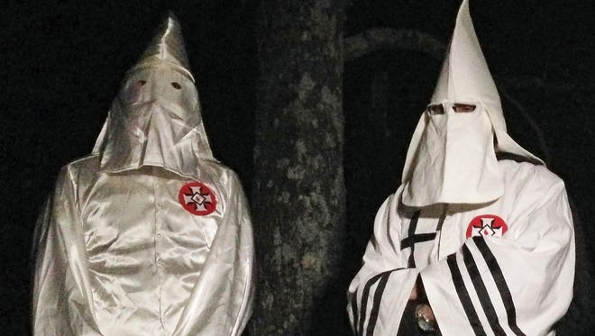 """In this Friday, Dec. 2, 2016 photo, two masked Ku Klux Klansmen stand on a muddy dirt road during an interview near Pelham, N.C. The KKK and other white extremist groups don't like being called """"white supremacists,"""" a phrase that dates to the earliest days of white racist movements in the United States. (AP Photo/Jay Reeves)"""