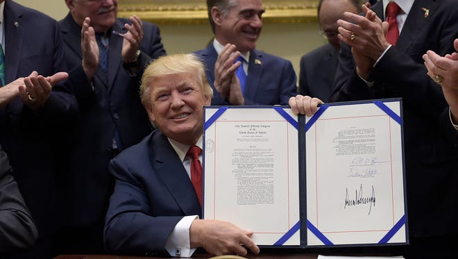 President Donald Trump hold up the Veterans Choice Program Extension and Improvement Act that he signed,  Wednesday, April 19, 2017, in the Roosevelt Room of the White House in Washington.