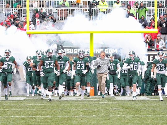 Zanesville native and former Ohio State defensive coordinator Mark Dantonio leads his Michigan State Spartans on the field for Saturday's game against the Buckeyes.